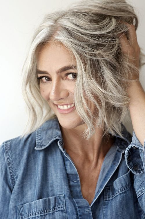 woman with silver-gray hair holding hand in her hair, smiling