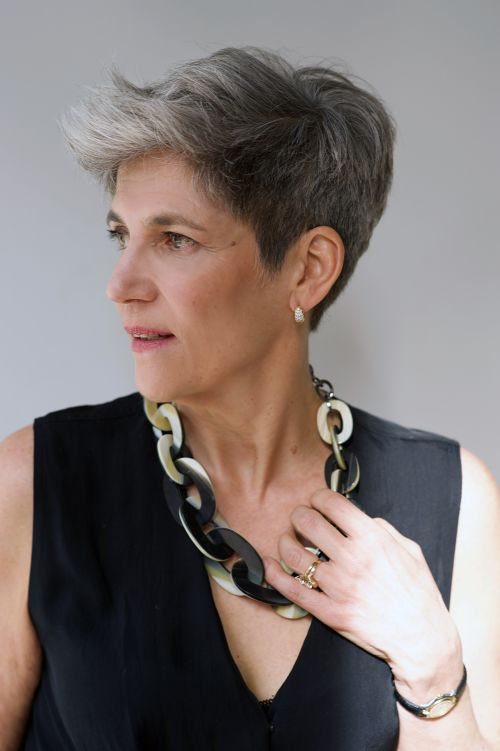 woman with short gray haircut with a hand on her large necklace glancing sideways